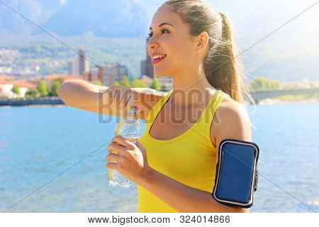 Thirsty Fitness Woman Opens Bottle Of Water After Training Outdoor. Fit Woman Using Smartphone Fitne