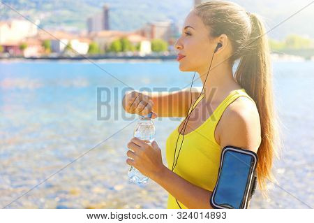 Thirsty fitness woman opens bottle of water after training outdoor. Fit woman using smartphone fitness app on armband for listening to music or as activity tracker. poster