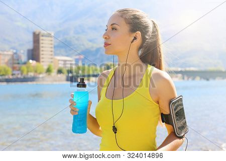 Thirsty Female Athlete With Armband For Smart Phone Holding Power Drink And Looking Away Outdoors.