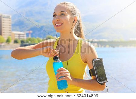 Happy Cheerful Female Athlete With Armband For Smart Phone Open Power Drink Bottle After Daily Train