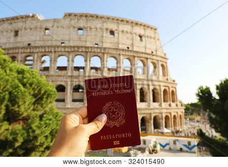 Citizenship Concept: Hand Hold Italian Passport In Front Of Colosseum In Rome.