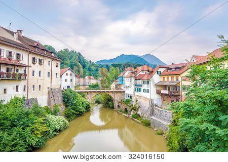 View At The Old Part Of Skofja Loka With Cappuchin Bridge Over Selca Sora River In Slovenia
