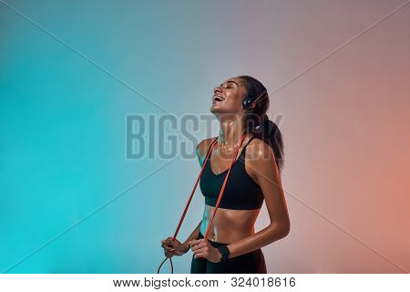 Great Workout Side View Of Happy Young Woman In Headphones Holding Jumping Rope On Shoulders And Kee