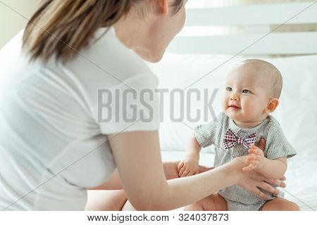 Mother And Baby Happily Tease Each Other On A White Bed - Mom And Baby Concept