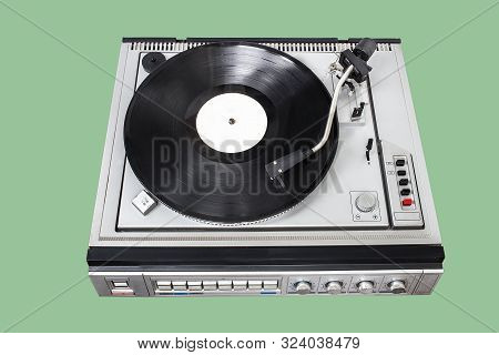 Vintage Record Player With Radio Tuner On Green Background