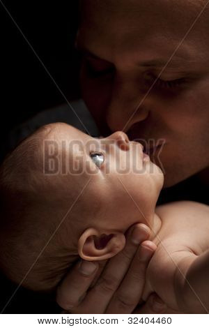 Happy Young Father Holding His Mixed Race Newborn Baby Under Dramatic Lighting.