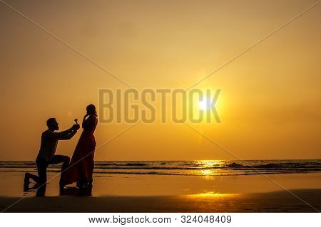 Romantic Marriage Proposal At The Seaside At Sunset On The Beach Sea. Young Couple In Love Female Sa
