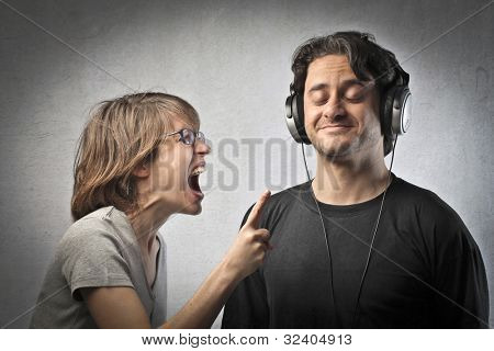 Angry wife screaming against a serene husband listening to music
