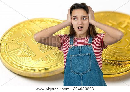 Girl On The Background Of Bitcoin. Thinking About Question, Pensive Expression, Looks Incredulous. C