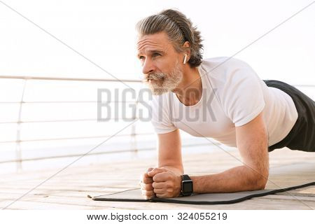 Image of serious mature man in sportswear using earpod while doing exercise near seaside in morning