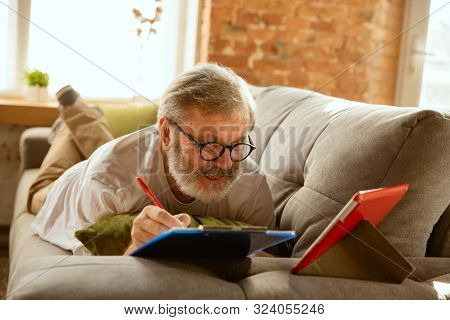 Senior Man Working With Tablet At Home - Concept Of Home Studying. Caucasian Male Model Lying On Sof