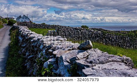 Limestone Fences Beside A Rural Road On Inis Oirr Island With Houses And The Sea In The Background,