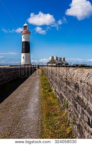 Lighthouse And A Path Between Limestone Fences On The Island Of Inis Oirr, Wonderful Sunny Day With