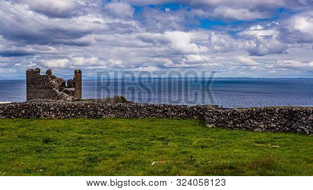 Beautiful View Of A Limestone Fence On Inis Oirr Island With The Ruined Castle Tower (caisleán Ui Bh