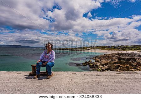 Mexican Woman Sitting On The Shore Of The Pier Of Inis Oirr Island With The Beach, Limestone Rocks A