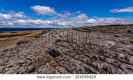 View Of The Rocky Limestone Coast, A Road And Stone Fences On The Island Of Inis Oirr With The Sea I
