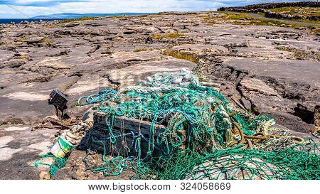 Large Amount Of Marine Litter, Such As Fishing Nets, Ropes, Wood, Boats And Plastic Boxes On The Roc