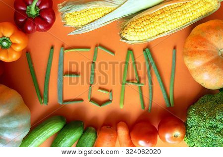 Frame Of Fresh Vegetables With Vegan Word On Orange Background. Vegan Word Made Of Green Onion. Asso
