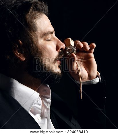Brutal Bearded Man With Modern Hairstyle In Classic Business Suit Smells Small Bottle Of Perfume Fra