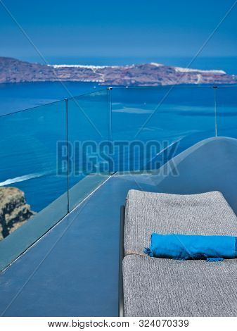 Santorini, Greece - July 30 2019 Unfolded Chaise Longue With Rolled Blanket On Balcony Over Blue Sea