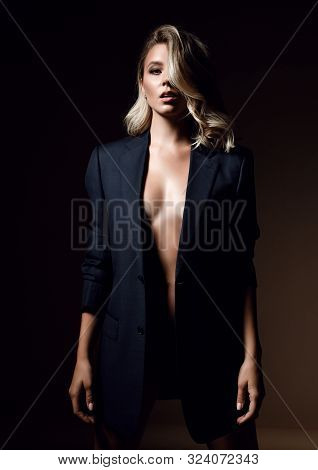Young Sensual Woman With Her Long Blonde Hair Covering Half Of Her Face Is Standing In Formal Jacket