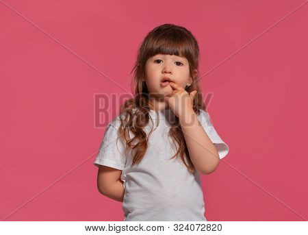 Close-up Portrait Of A Little Brunette Girl Dressed In A White T-shirt Posing Against A Pink Studio