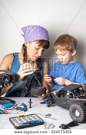 Women In The Mens Work: Mom Helps Her Son With Fixing A Radio-controlled Buggy Model.