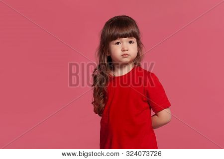 Close-up Portrait Of A Little Brunette Girl Dressed In A Red T-shirt Posing Against A Pink Studio Ba