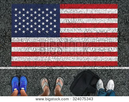 People Legs Is Standing On Asphalt Road Next To Flag Of The United States And Border