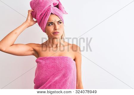 Young beautiful woman wearing shower towel after bath over isolated white background confuse and wonder about question. Uncertain with doubt, thinking with hand on head. Pensive concept.