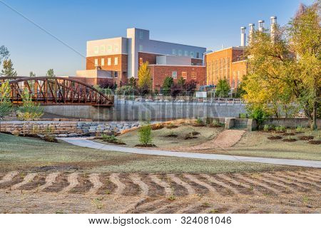 landscaping and restoration of natural grass and vegetation in a newly constructed whitewater park on the Poudre River in downtown of Fort Collins Colorado with Powerhouse Energy Campus in background