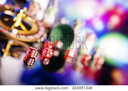 Casino Theme.  Roulette, Dice And Poker Chips On A Colorful Bokeh Background.