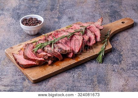 Slices Of Medium Rare Roast Beef Meat On Wooden Cutting Board, Pepper And Rosemary Twigs On Gray Mar