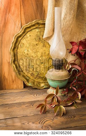 Old Kerosene Lamp And Tray And Red Leaves Of Grapes On A Wooden Table In Rustic Style