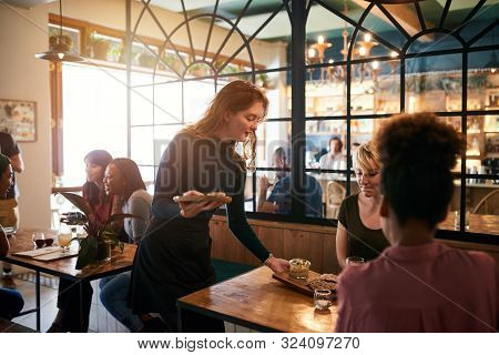Young Waitress Serving Food To A Table Of Smiling Customers