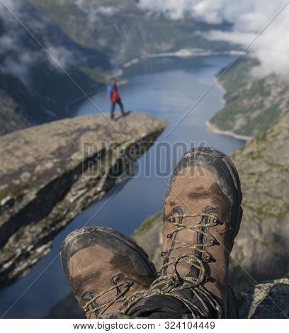 Hiking Boots In Foreground. Troll Tongue (trolltunga) Rock With Little Man And Norway Fjord In The B
