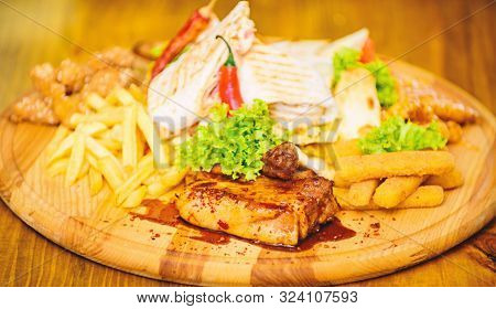Snack For Beer. Wooden Board French Fries Fish Sticks Burrito And Meat Steak Served With Salad. Pub