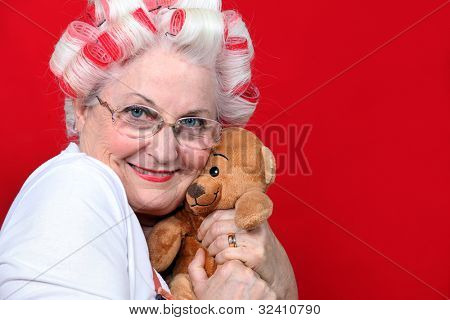 An old woman with hairroller on hugging a teddy bear.