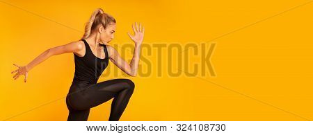 Sport And Fitness. Slim Girl Jumping Working Out In Studio On Yellow Background. Panorama, Side View