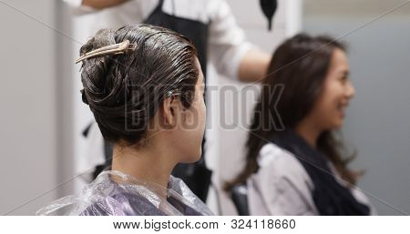 Friends chat and wait for the color dye on hair in salon