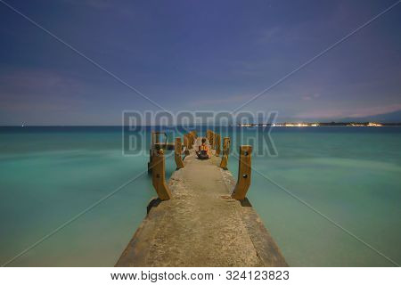 Young Woman Practices Meditation On The Pier. Long Exposure Night Sky. Gili Meno Indonesia