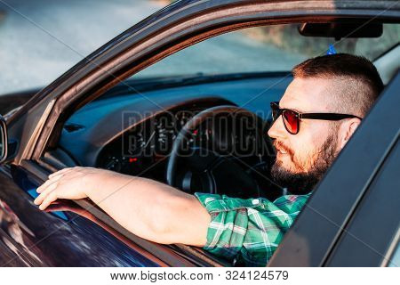 Cute, Bearded Man With Eyeglasses Driving A Car. Looking Trough The Window.transportation Concept