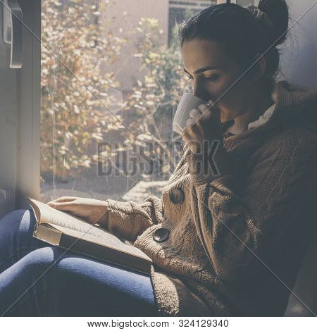 Young Brunette Woman Drinking A Cup Of Tea Or Coffee And Reading A Book. Female Sitting At Home By T