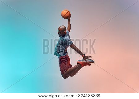 Slam Dunk. Full Length Of Young African Backetball Player Jumping Against Colorful Background