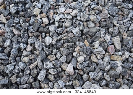 Gravel Rock Texture. Crushed Stone And Gravel On The Ground. Texture Background Brown Stones On A Bl