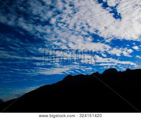 Clouds Sky And Mountain Silhouette Merge In The Sky Blue. A Skyscape Deep Blue With Woolly White Fle