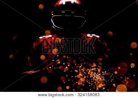 American football player standing in rugby helmet and holding rugby ball against firework bursting sparkle background