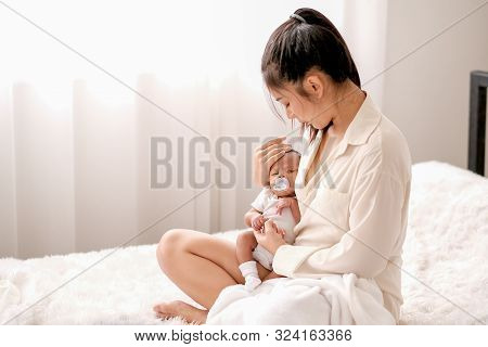 Soft Blur Image Of Beautiful Asian Mother Hold Her Newborn Baby With Baby Teat On The White Bed.