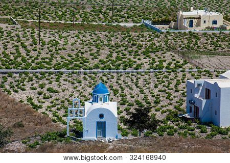 Vineyards And The Holy Trinity Church Located In Akrotiri Village On The Santorini Island
