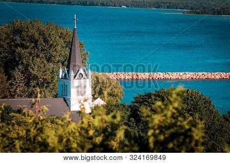 Mackinac Island Mi /usa - July 9th 2016: Sainte Annes Church Peaking Out Above The Tree Line On Mack